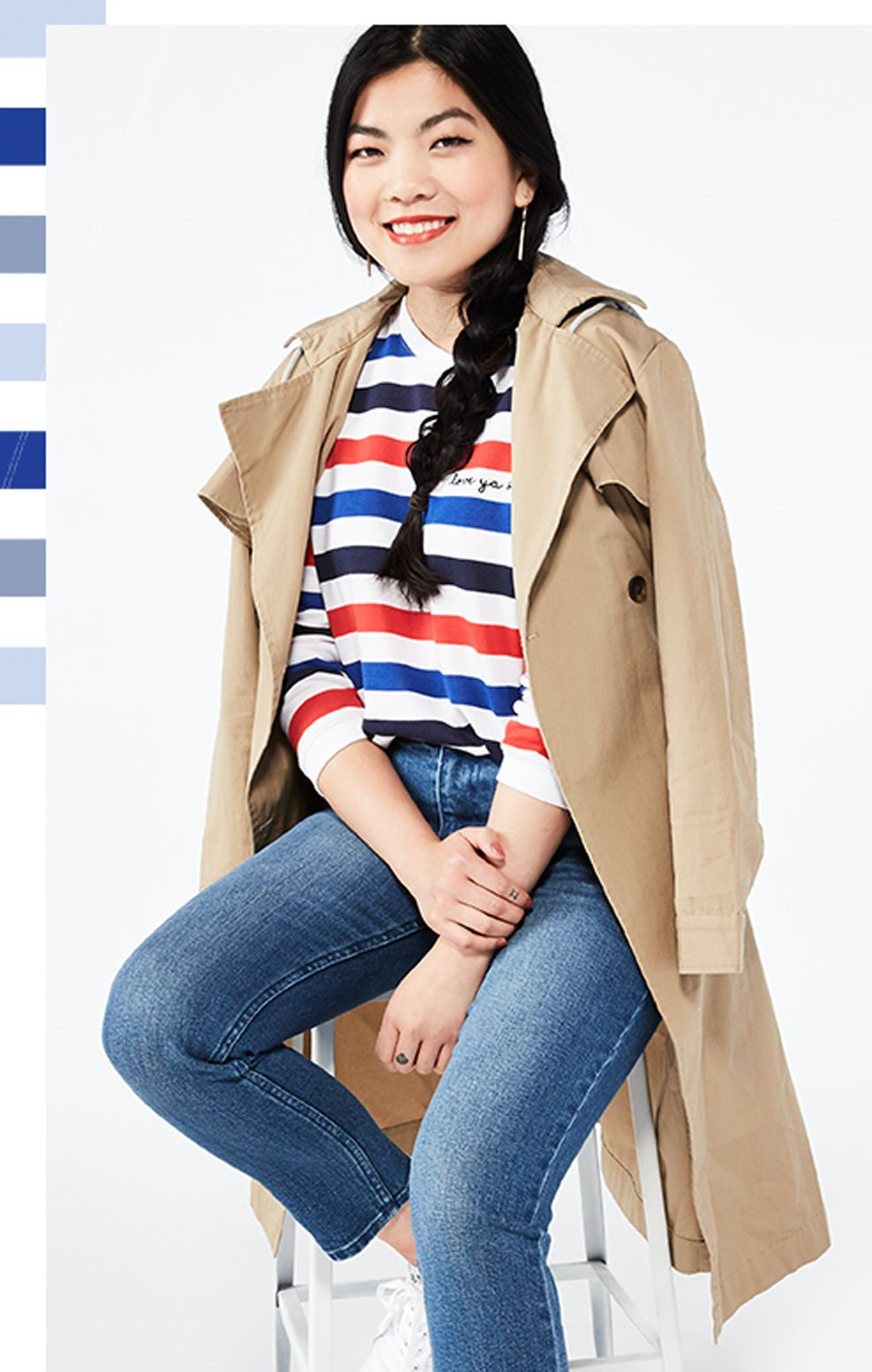 woman (Carrie) sitting on a stool in jeans and a striped shirt with a trenchcoat over her shoulders