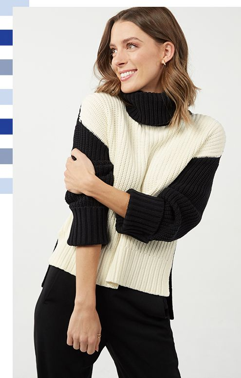 woman (Sarah) wearing a high contrast, peach and ebony knit sweater, smiling while looking away and up