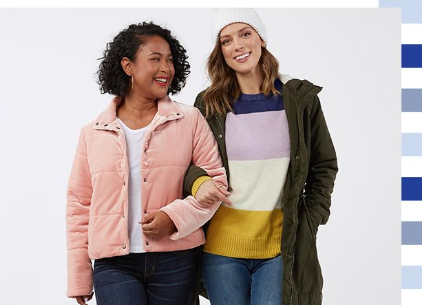 two women (Alexandra and Sarah) smiling with arms linked and fall jackets